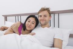 爱恋的夫妇画象在床上 免版税库存图片