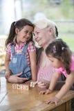 爱恋的对孙女的祖母教的演算在桌上在房子里 免版税库存图片