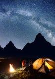 爱恋的对-人和女孩坐面对面在前面帐篷在篝火附近下在晚上发光满天星斗的天空 免版税库存图片