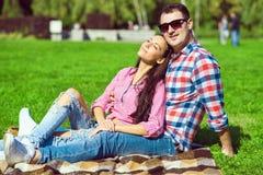 年轻爱恋的愉快的夫妇在控制中衬衣、牛仔裤和白色运动鞋坐绿色草坪 库存图片