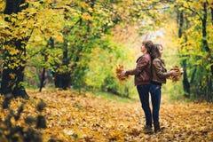 爱恋的愉快的夫妇在秋天在拿着秋天槭树的公园在手离开 库存图片