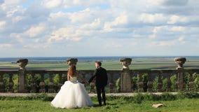 爱恋的新郎走与绿色草坪的美丽的新娘在老石楼梯栏杆附近 与大云彩的壮观的蓝天 影视素材