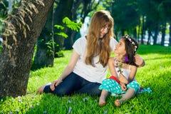爱恋的母亲和她的小女儿在庭院里 免版税库存图片
