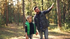 爱恋的爸爸的慢动作谈话与他的关于站立在晴朗的秋天天,打手势和微笑的森林里的自然的儿子 影视素材