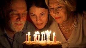 爱恋的资深夫妇和他们的女儿在家庆祝与蛋糕 拥抱和吹灭蜡烛 股票录像
