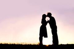 爱恋的年轻夫妇亲吻的外部剪影在太阳的日期 图库摄影