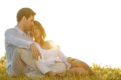 爱恋的年轻夫妇坐草反对清楚的天空 免版税库存照片
