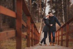 爱恋的年轻夫妇愉快室外在舒适在森林里一起温暖步行 图库摄影