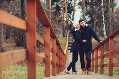 爱恋的年轻夫妇愉快室外在舒适在森林里一起温暖步行 免版税库存图片