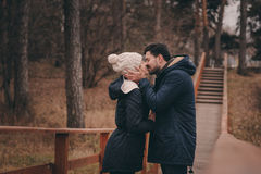 爱恋的年轻夫妇愉快室外在舒适在森林里一起温暖步行 免版税库存照片