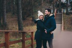 爱恋的年轻夫妇愉快室外在舒适在森林里一起温暖步行 库存照片