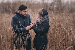 爱恋的年轻夫妇愉快室外在舒适在森林里一起温暖步行 库存图片
