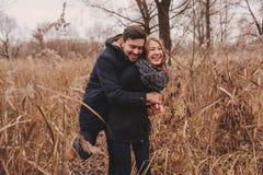 爱恋的年轻夫妇愉快室外在舒适在秋天森林里一起温暖步行 免版税图库摄影