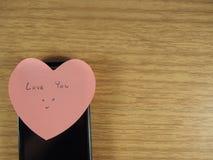 爱您有在贴纸笔记和黑手机的微笑的面孔文字的在木背景 免版税库存图片