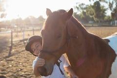 爱抚一匹马的车手男孩在大农场 免版税库存照片