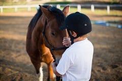 爱抚一匹马的车手男孩在大农场 库存照片