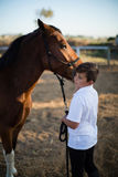 爱抚一匹马的车手男孩在大农场 库存图片