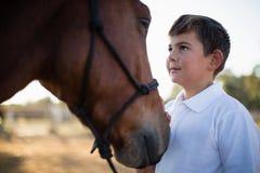 爱抚一匹马的车手男孩在大农场 免版税图库摄影