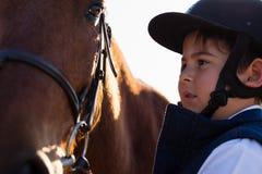 爱抚一匹马的车手男孩在大农场 免版税库存图片