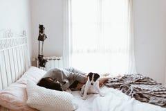 爱抚她的拉布拉多小狗的年轻哀伤的深色的妇女在卧室 库存图片