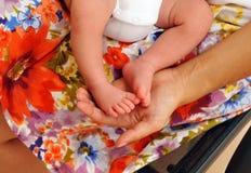 爱抚她的有柔软的第一个婴孩的脚的妇女的扣人心弦的场面 免版税图库摄影