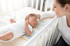 爱抚她的婴孩的愉快的微笑的母亲在轻便小床 免版税图库摄影