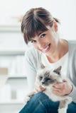 爱抚她的birman猫的妇女 免版税库存图片