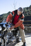 爱抚摩托车的人 库存图片