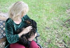 爱拥抱达克斯猎犬在公园 免版税库存图片