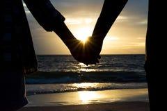 爱敲响婚姻的符号 现出轮廓男人和妇女手藏品夫妇  免版税库存照片