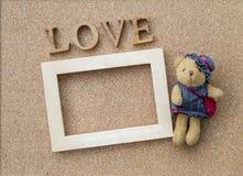 爱文本和木制框架与一点逗人喜爱的熊 库存照片