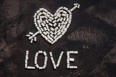 爱文本由白色心脏蛋白软糖,爱的装饰制成 库存照片