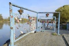 爱新婚佳偶和恋人垂悬的锁篱芭的在河附近 牢固的关系和永恒爱的标志 免版税库存照片