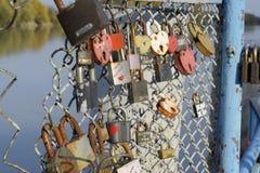 爱新婚佳偶和恋人垂悬的锁篱芭的在河附近 牢固的关系和永恒爱的标志 免版税库存图片