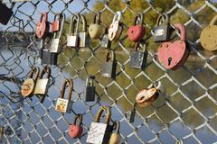 爱新婚佳偶和恋人垂悬的锁篱芭的在河附近 牢固的关系和永恒爱的标志 库存图片