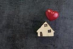 爱有陶瓷微型房子的房子和在d的红色心脏形状 库存照片