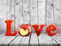 爱标志用在木桌上的红色苹果 免版税图库摄影