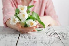 爱浪漫史,女孩的标志赠送了白色郁金香花束  免版税库存图片
