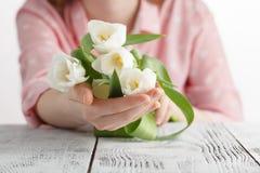 爱浪漫史,女孩的标志赠送了白色郁金香花束  图库摄影
