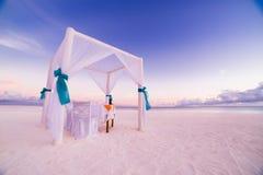 爱海滩 浪漫海滩晚餐、白色沙子和白色帐篷 夫妇和蜜月背景概念的日出或日落颜色 免版税库存照片
