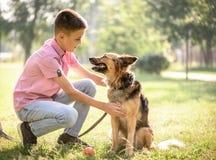 爱犬与室外的男孩的杂种护羊狗 免版税库存照片