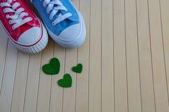 爱用不同的运动鞋和绿色心脏的背景 免版税库存图片