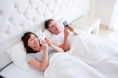 爱的中部在卧室,愉快的人民变老了微笑和观看某事在她的modile电话的夫妇 免版税库存图片