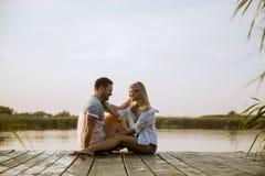 爱的夫妇坐在湖的码头 免版税库存照片