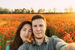爱的夫妇照相selfie在鸦片花草甸 图库摄影