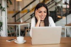 爱的妇女喝咖啡和闲谈在便携式计算机上 免版税库存图片