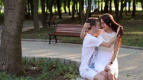爱的柔和的年轻人坐一条长凳在夏天晴朗的公园 慢的行动 股票视频