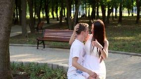 爱的柔和的青年人坐一条长凳在公园,他们开心 股票录像