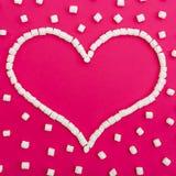 爱的标志由蛋白软糖制成在桃红色背景 心脏 平的位置 顶视图 库存照片