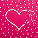 爱的标志由蛋白软糖制成在桃红色背景 心脏 平的位置 顶视图 图库摄影